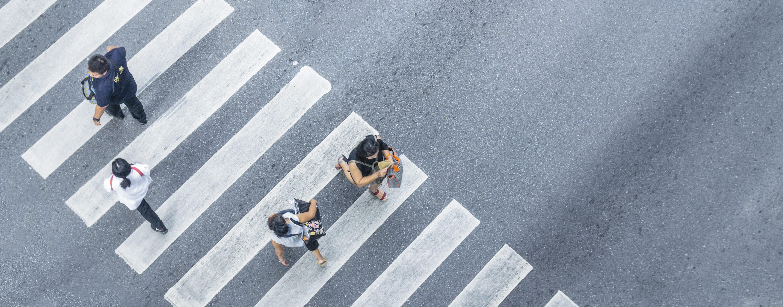 four pedestrians walk on crosswalk